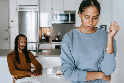 Crop unhappy black woman with boyfriend at home