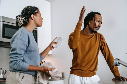 Discontented black couple arguing in kitchen at home