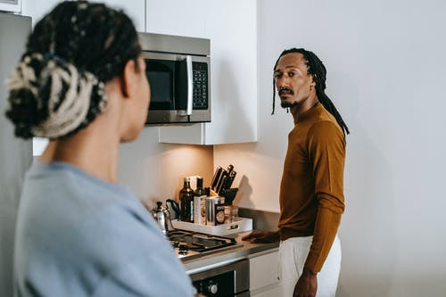 Anonymous ethnic female speaking with boyfriend with dreadlocks while looking at each other in house