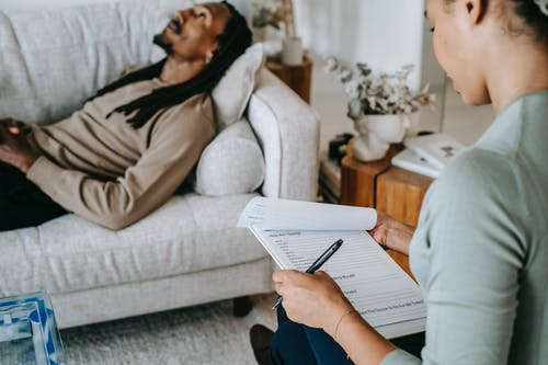Crop black woman with questionnaire interacting with boyfriend on couch
