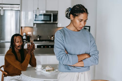 Young discontented African American female with folded arms against male partner at kitchen table during quarrel