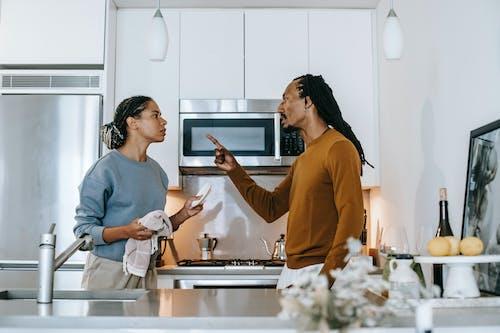 Annoyed black man threatening girlfriend during conflict in kitchen