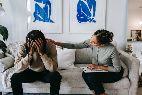 Black woman consoling anonymous unhappy boyfriend on sofa at home