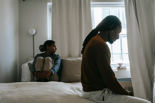 Young frustrated black man with dreadlocks near unhappy girlfriend sitting on bed during conflict