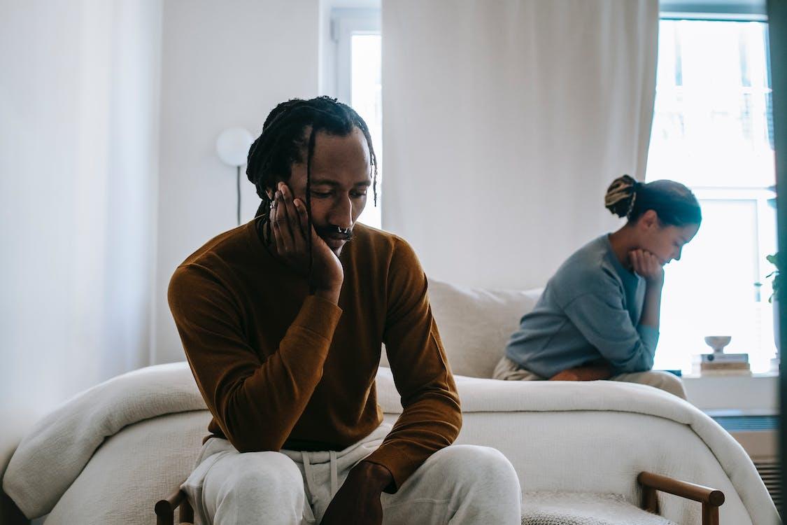 Upset black couple sitting apart at home