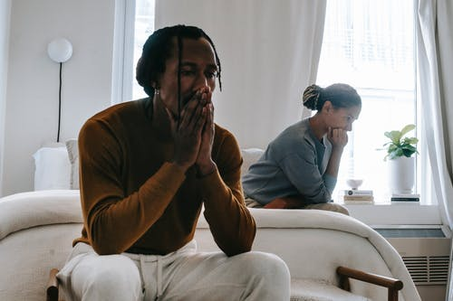 Wistful concerned African American couple in casual clothing sitting on bed at home after having quarrel