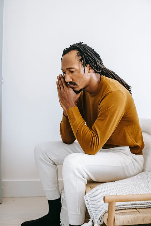Side view concerned depressed African American male wearing casual outfit touching face in frustration and sitting on couch at home
