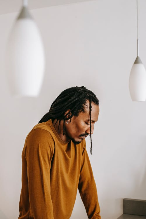 Sad black man standing with eyes closed in light room