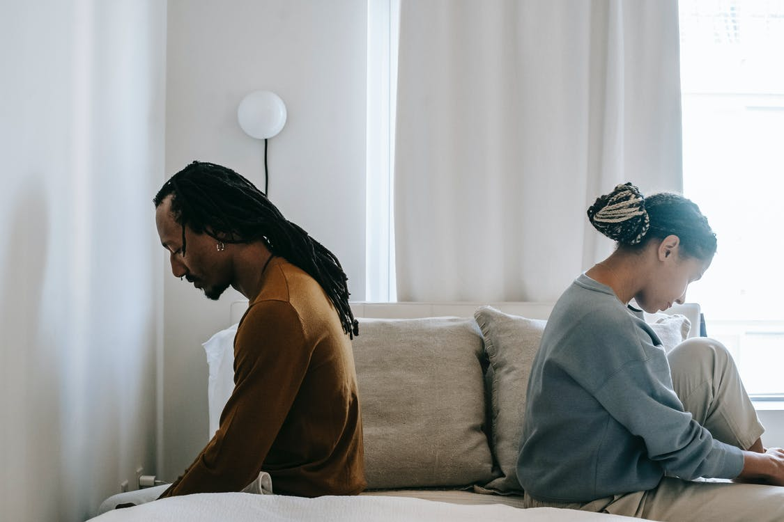 Side view unhappy sorrowful African American couple sitting on bed back to back after having argument