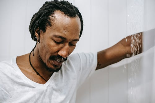 Depressed black man standing in shower cabin
