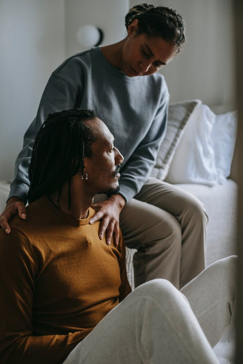Attentive loving African American female supporting and touching shoulders of stressed frustrated husband while sitting in light bedroom