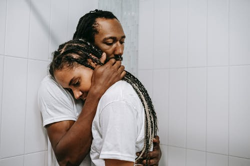 Stressed sad African American couple in white shirts embracing each other in light bathroom