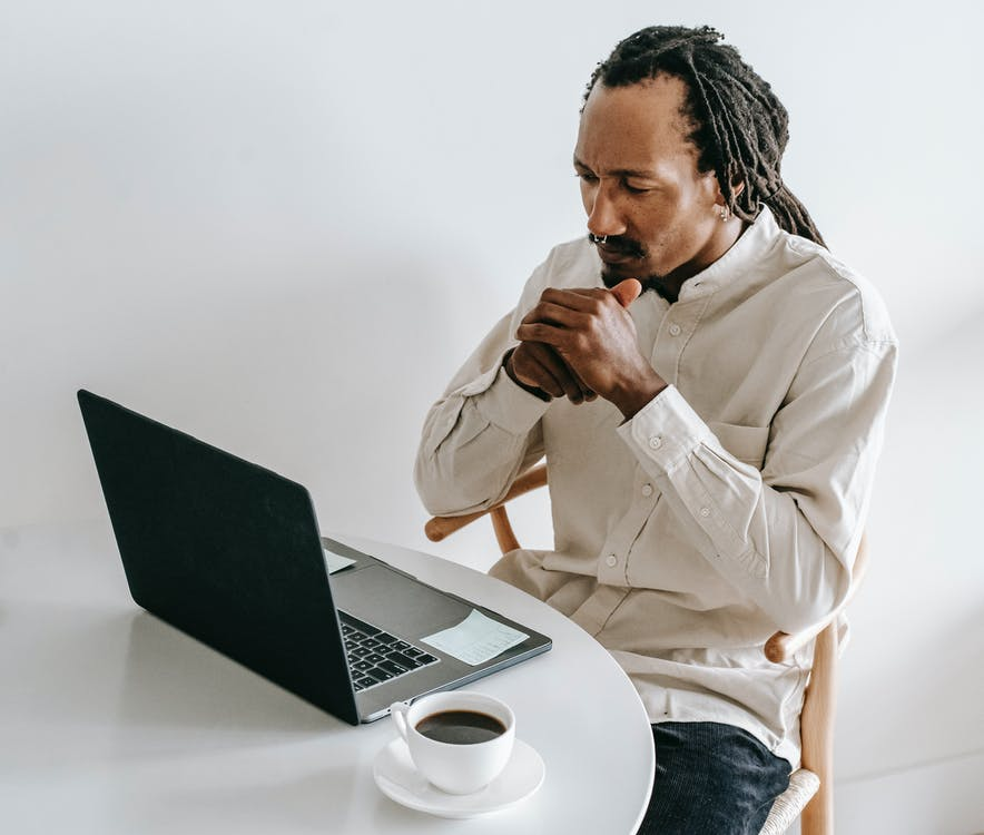 Concentrated adult African American male in formal wear sitting at table with cup of coffee and watching video on netbook in light room