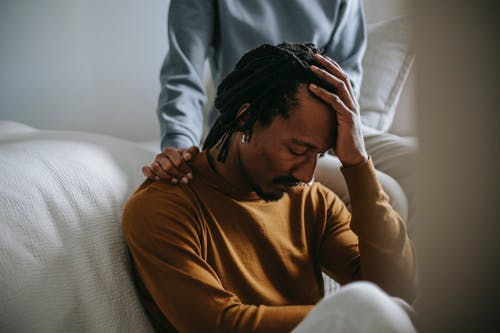 Worried depressed African American male touching head nervously and sitting with eyes closed near supporting wife in bedroom