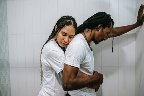 Side view sad loving African American female in white shirt standing behind and embracing depressed unhappy husband in bathroom