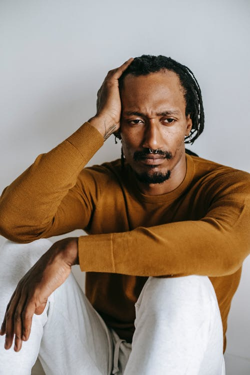 Uncertain disappointed African American male in casual clothes touching head and looking away in frustration while sitting on floor against white wall