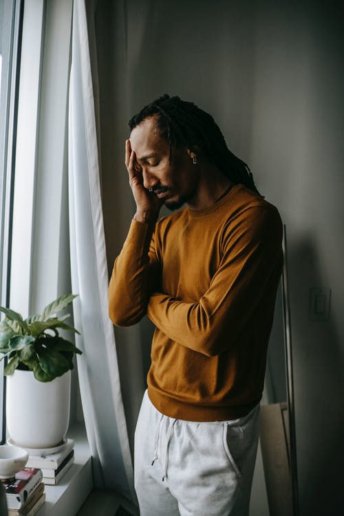 Depressed black man touching face in frustration near window