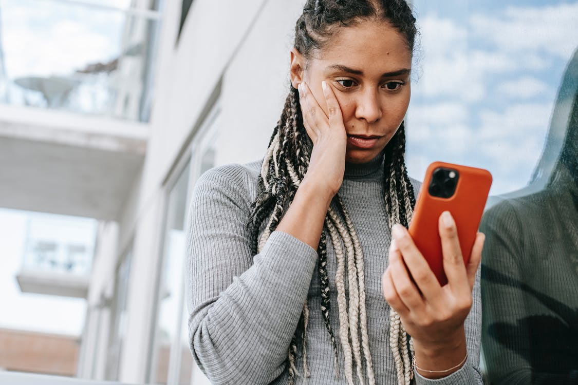 Crop serious African American female with dreadlocks touching cheek in contemplation and browsing mobile phone on street