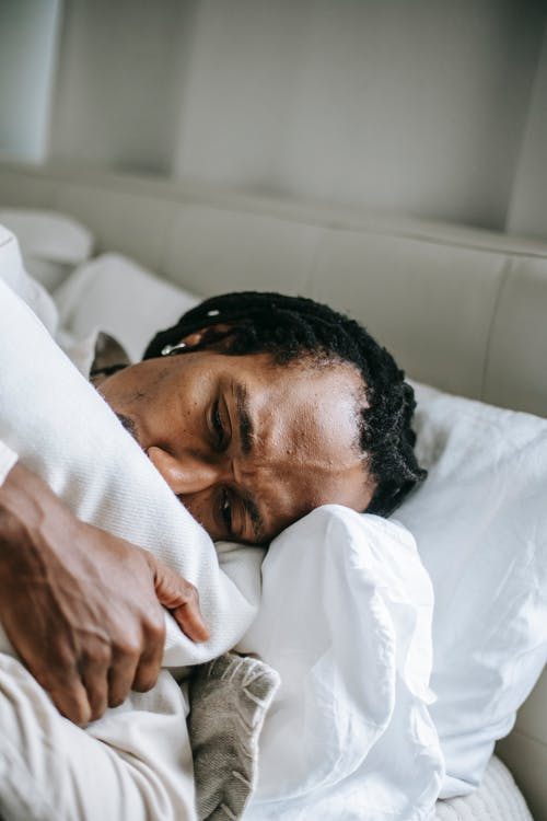 Embarrassed unhappy African American male lying on bed and hugging pillow in dismay in light bedroom