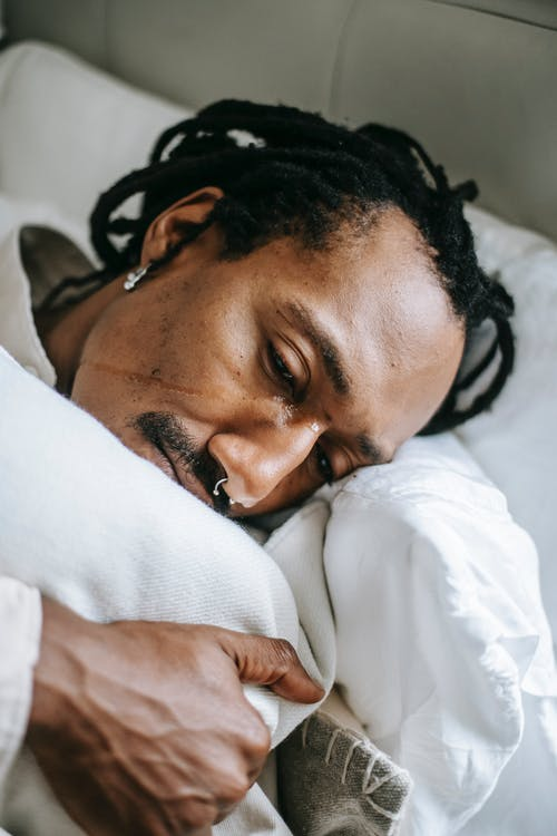 From above pondering stressed African American male hugging pillow and looking away in sad thoughts while lying on bed