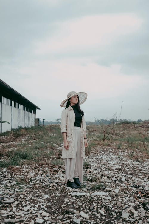 Woman in White Long Sleeve Dress Standing on Brown Dried Leaves