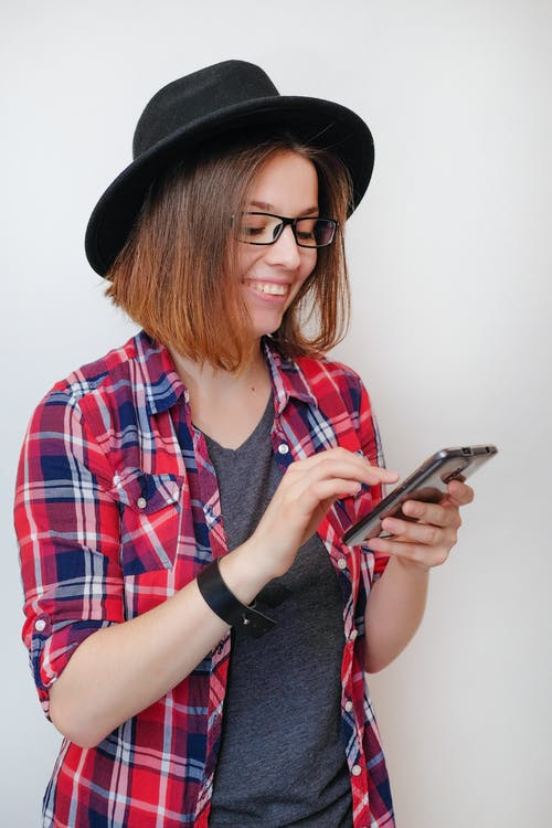 Happy young female in casual outfit and trendy hat browsing modern mobile phone against white wall