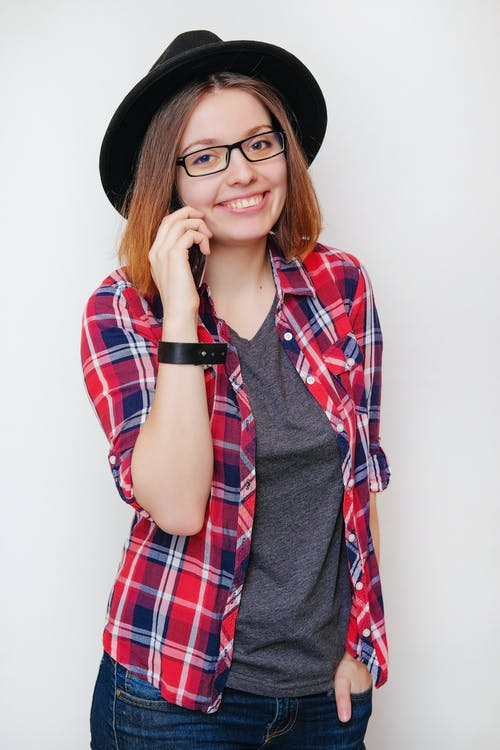 Content young woman talking on smartphone in studio