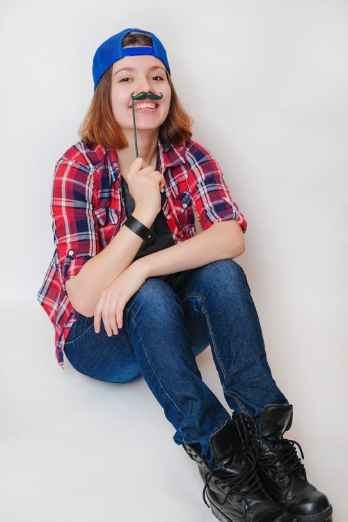 Smiling young female in casual wear holding funny artificial mustaches on stick above upper lips while sitting on floor in light studio and looking at camera happily