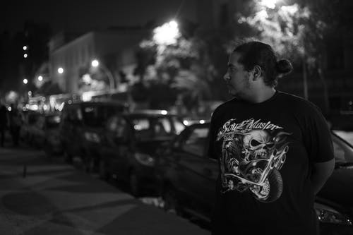 Grayscale Photo of Man Standing in Front of Vehicle