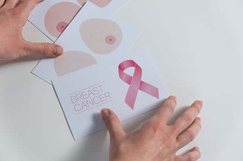 Person Holding White and Pink Card