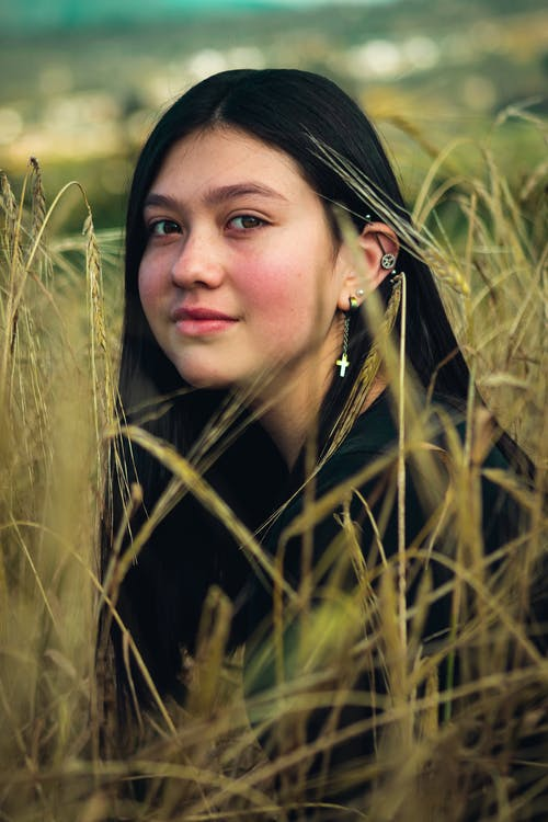 Woman in Black Hat and Black Leather Jacket on Green Grass Field