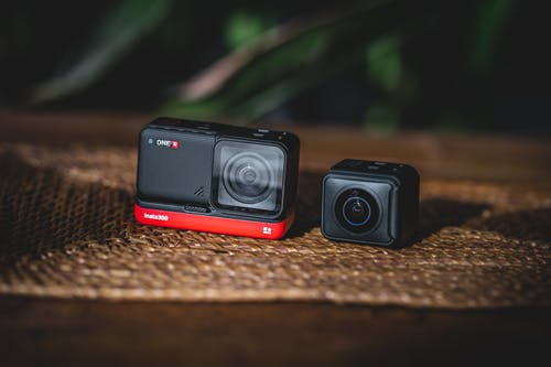 Black and Red Camera on Brown Surface