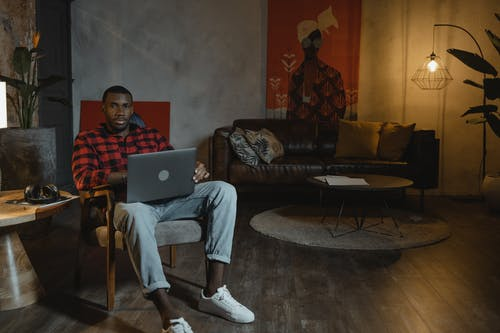 Man in Red and Black Checkered Dress Shirt Sitting on Couch Using Macbook