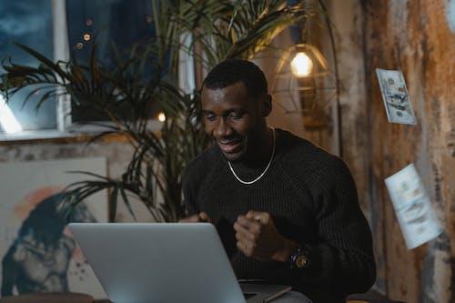 Man in Black Sweater Using Laptop