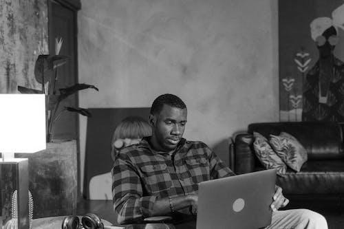 Man in Plaid Shirt Using Laptop