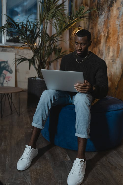 Man in Black Long Sleeve Shirt and Blue Denim Jeans Sitting on Blue Chair Using Silver Laptop