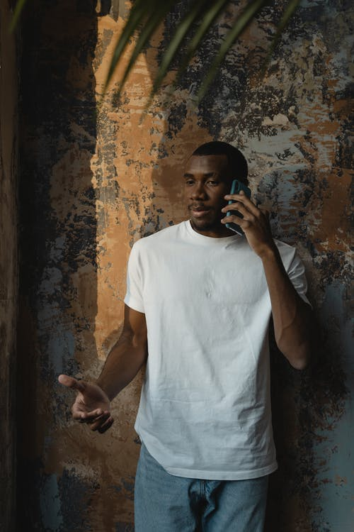 Man in White Crew Neck T-shirt Having a Phone Call