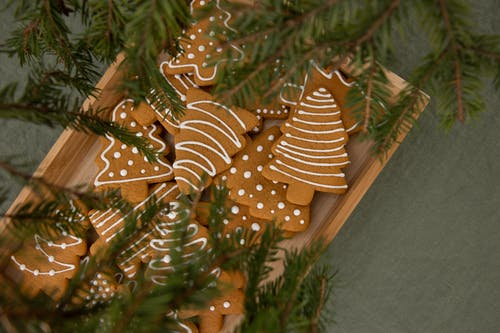 Selective Focus Photo of Brown Christmas Tree-Shaped Gingerbread Cookies in a Wooden Crate