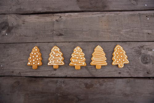 Brown Christmas Tree-Shaped Gingerbread Cookies on Wood Background
