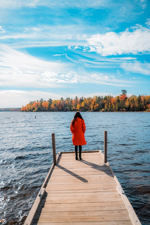 Woman in Red Long Sleeve Shirt Standing on Wooden Dock