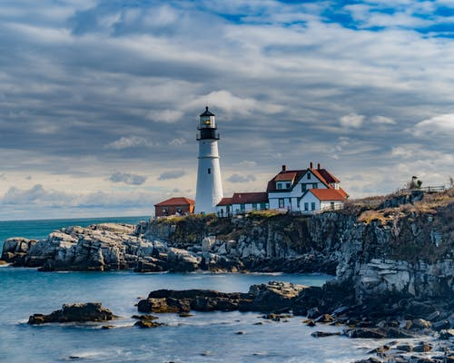 White and Black Lighthouse on Rocky Shore Under Cloudy Sky