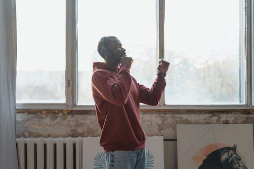 Man in Red Hoodie Standing Near Window