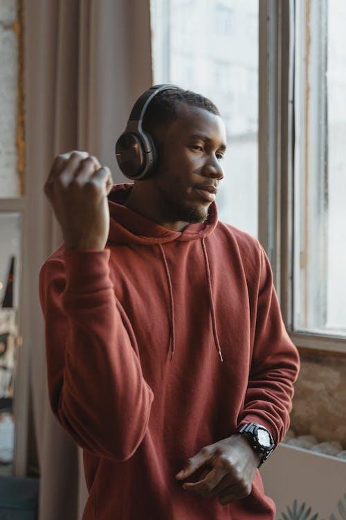 Man in Red Hoodie Wearing Black Headphones