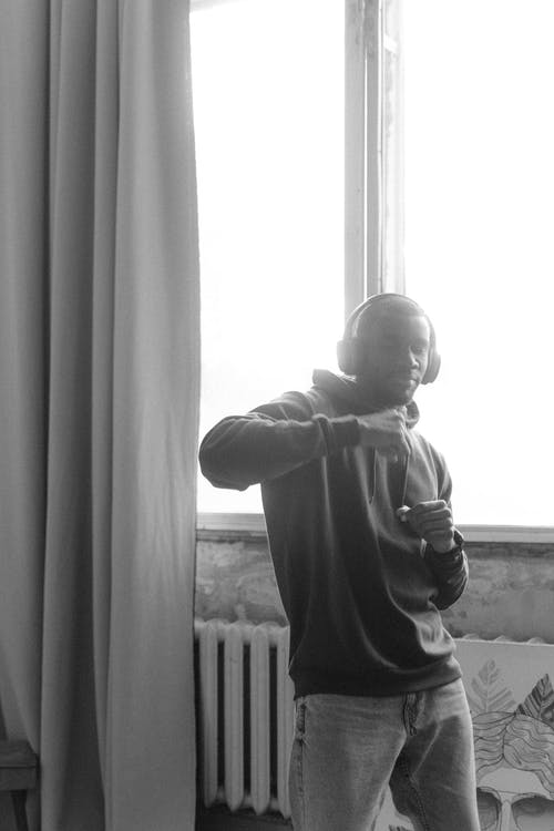 Grayscale Photo of Child in Hoodie Standing by the Window