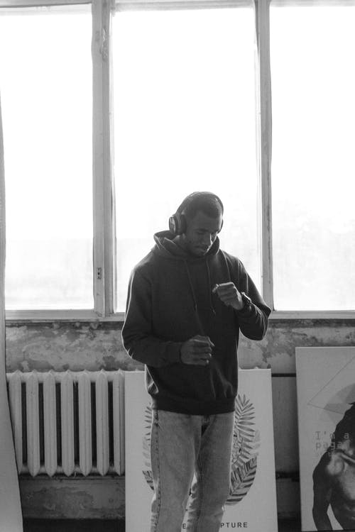Grayscale Photo of Man in Hoodie Standing Near Window