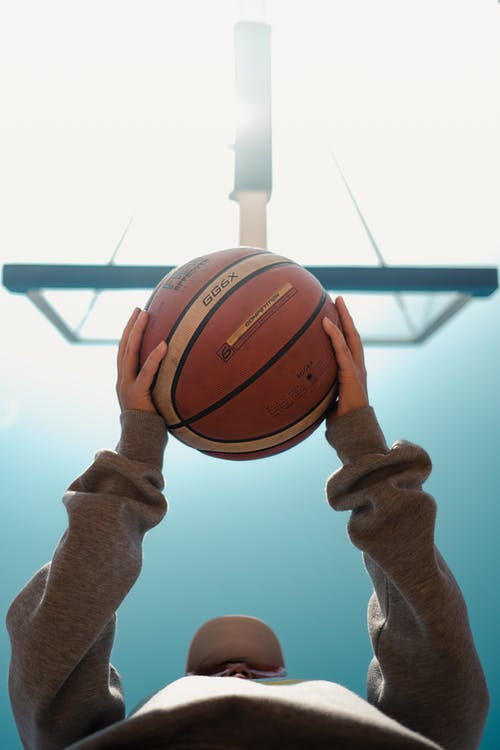 Person Holding Brown Basketball Under Blue Sky