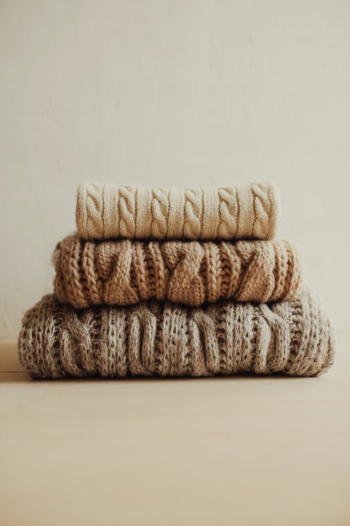 Stack of knitted sweaters on white surface