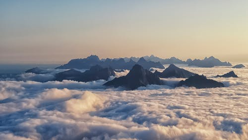 Breathtaking scenery of rocky mountains range over white thick fluff clouds at sunset