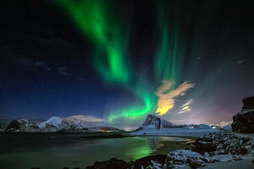 Starry sky with northern lights and sea in mountainous terrain