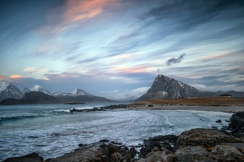 Powerful ocean with foamy waves washing sandy beach surrounded by rocky formations and mountains against cloudy sunset sky in Lofoten Archipelago